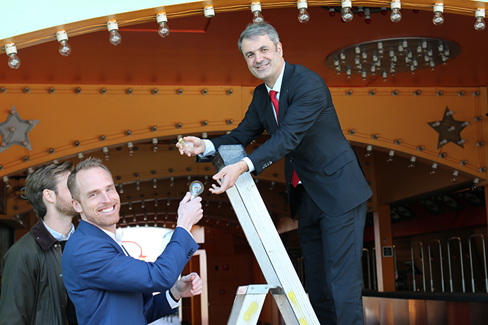 Mr Balyan is standing on a ladder, recieving an LED lightbulb from Parks and Resorts President and CEO