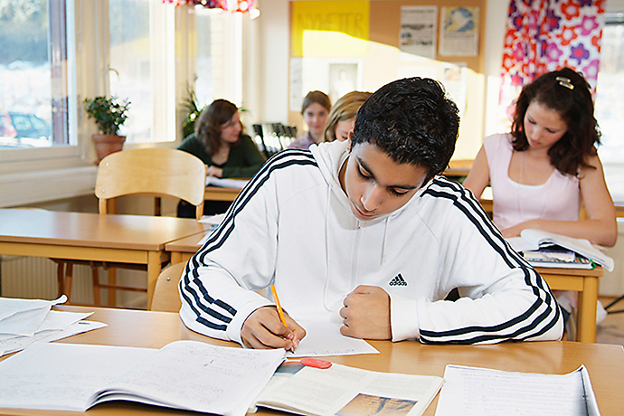Young boy studying in a classrum.