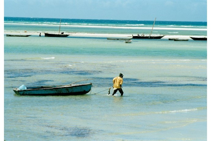 Man with a boat on a beach.