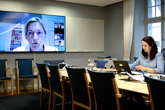 Minister for Gender Equality Åsa Lindhagen is sitting in a conference room looking at a computer.