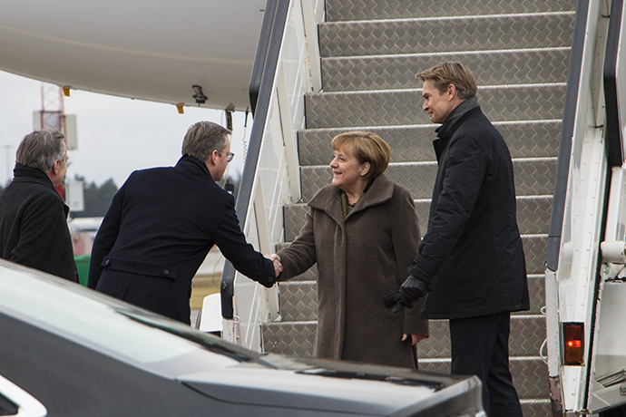 Mikael Damberg shakes hands with Angela Merkel as she has decended the stairs of her aircraft.