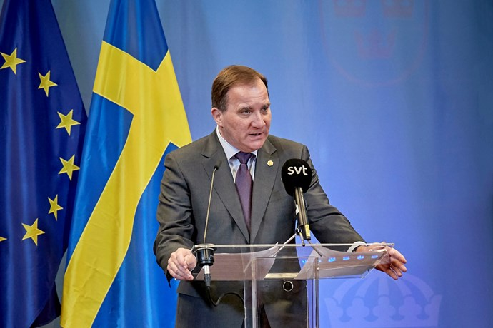 Prime Minister Stefan Löfven is standing in front of journalists during a press conference.