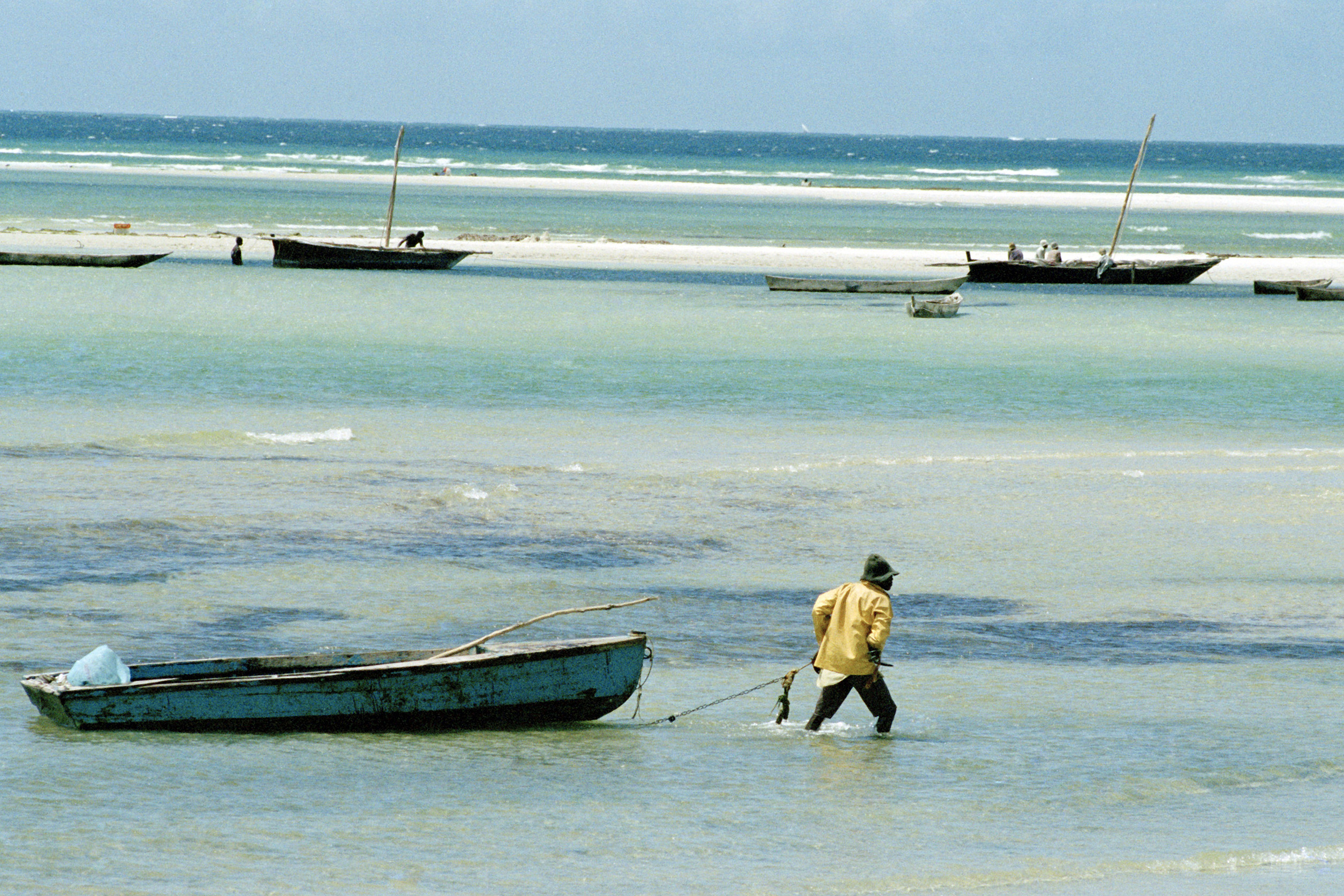 Fisherman dragging boat in shallow water
