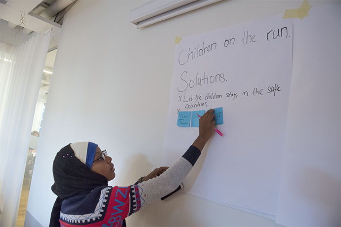 A girl writing on a white board in the youth delegates workshop