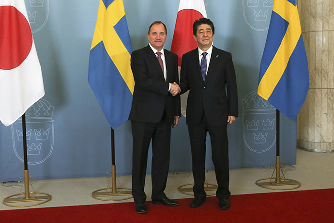 The Prime Minister Stefan Löfven and Prime Minister Shinzo Abe shake hands in front of flags.